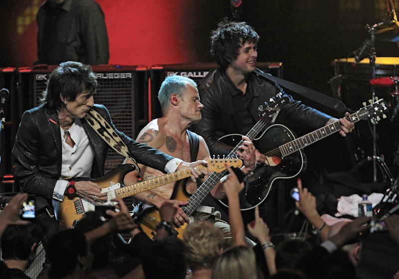 """Ronnie Wood, left, Mike """"Flea"""" Balazary, center, and Billy Joe Armstrong perform in the finale of the 2012 Rock and Roll Hall of Fame inductions Sunday, April 15, 2012, in Cleveland. (AP Photo/Tony Dejak)"""