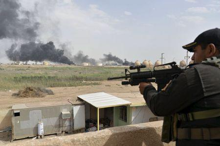 A member from the Iraqi security forces guards as smoke rises from Baiji oil refinery, north of Baghdad