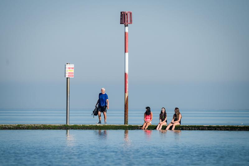 A man talks to three girls as they dip their feet in the saltwater lido on Friday in Margate (Photo: Leon Neal via Getty Images)