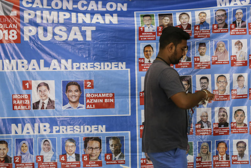 A man walks past a poster of PKR candidates during the Federal Territories PKR election in Kepong October 7, 2018. — Picture by Azneal Ishak