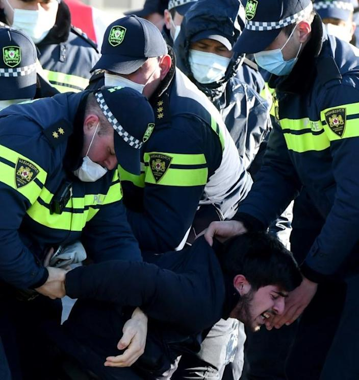 Georgian police detain an opposition supporter during the rally