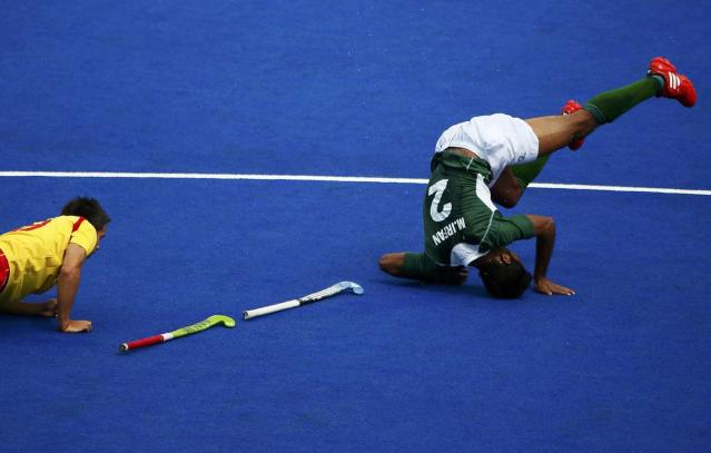Spain's Pablo Amat (L) and Pakistan's Muhammad Irfan fall during their men's Group A hockey match at the London 2012 Olympic Games at the Riverbank Arena on the Olympic Park in London July 30, 2012. REUTERS/Kai Pfaffenbach (BRITAIN - Tags: SPORT OLYMPICS SPORT FIELD HOCKEY)