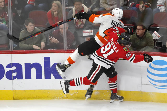 Chicago Blackhawks' Drake Caggiula (91) checks Philadelphia Flyers' Chris Stewart along the boards during the second period of an NHL hockey game Thursday, Oct. 24, 2019, in Chicago. (AP Photo/Charles Rex Arbogast)