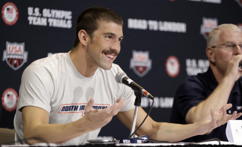 Michael Phelps speaks during a news conference at the U.S. Olympic swimming trials, Saturday, June 23, 2012, in Omaha, Neb. The trials starts on Monday. At right is Phelps' coach Bob Bowman. (AP Photo/Mark Humphrey)