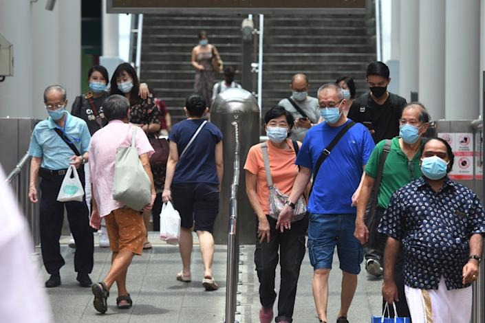 People wearing face masks are seen at a subway station in Singapore on Oct. 7, 2021. Singapore reported 3,483 new cases of COVID-19 on Thursday, bringing the total tally in the country to 116,864. (Photo by Then Chih Wey/Xinhua via Getty Images)