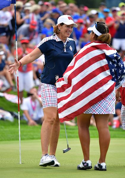 Juli Inkster, Captain of Team USA, celebrates with Lizette Salas on the 18th hole during the final day singles matches of The Solheim Cup on August 20, 2017 (AFP Photo/STUART FRANKLIN)