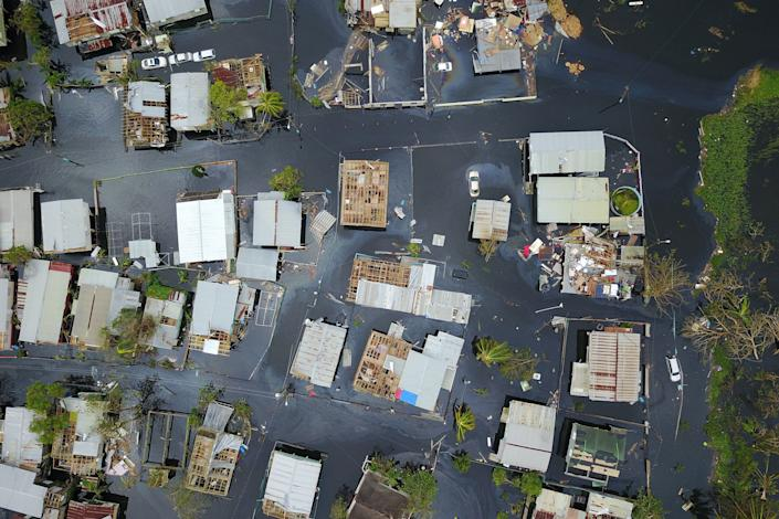An aerial view shows the flooded neighbourhood of Juana Matos in the aftermath of Hurricane Maria in Catano, Puerto Rico, on September 22, 2017. Puerto Rico battled dangerous floods Friday after Hurricane Maria ravaged the island, as rescuers raced against time to reach residents trapped in their homes and the death toll climbed to 33. Puerto Rico Governor Ricardo Rossello called Maria the most devastating storm in a century after it destroyed the US territory's electricity and telecommunications infrastructure. / AFP PHOTO / Ricardo ARDUENGO (Photo credit should read RICARDO ARDUENGO/AFP/Getty Images)