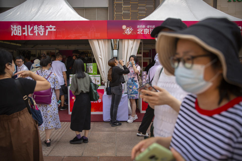 People wearing face masks to protect against the new coronavirus browse merchant tents at a government event aiming to stimulate consumer demand and consumption in Beijing, Saturday, June 6, 2020. China's capital is lowering its emergency response level to the second-lowest starting Saturday for the coronavirus pandemic. That will lift most restrictions on people traveling to Beijing from Wuhan and surrounding Hubei province, where the virus first appeared late last year. (AP Photo/Mark Schiefelbein)