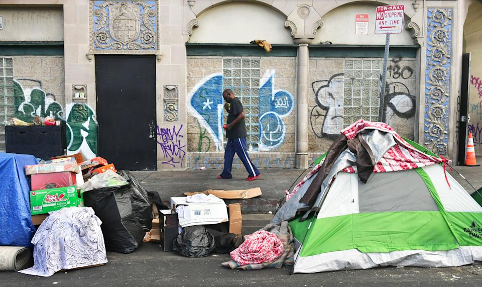 A man walks past tents housing the homeless on the streets in the Skid Row community of Los Angeles.