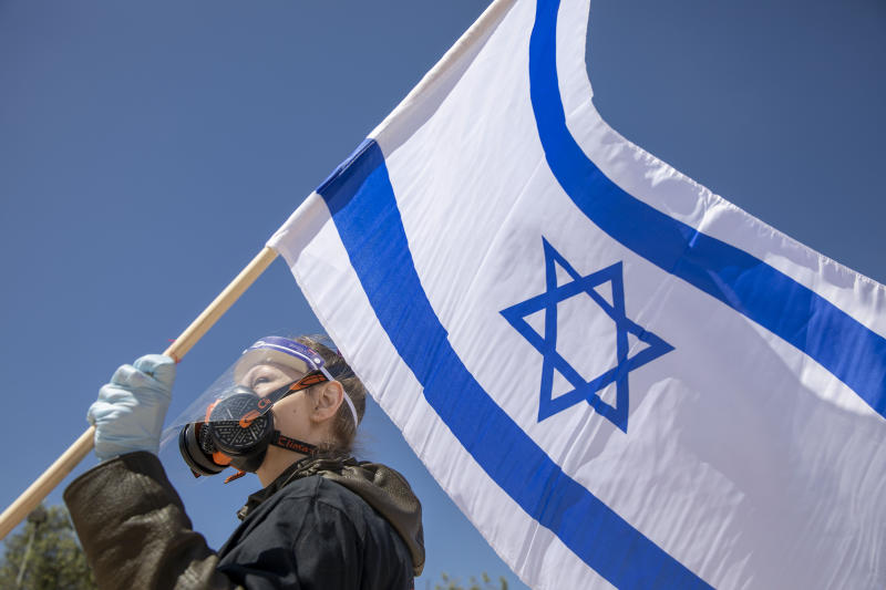 A protestor wearing a mask and gloves amid concerns over the country's coronavirus outbreak holds a flag during a protest by supporters of Prime Minister Benjamin Netanyahu in front of Israel's Supreme Court in Jerusalem, Thursday, April 30, 2020. Dozens of protesters rallied outside Israel's Supreme Court on Thursday against petitions to disqualify Benjamin Netanyahu from serving as prime minister while facing criminal indictments. (AP Photo/Ariel Schalit)