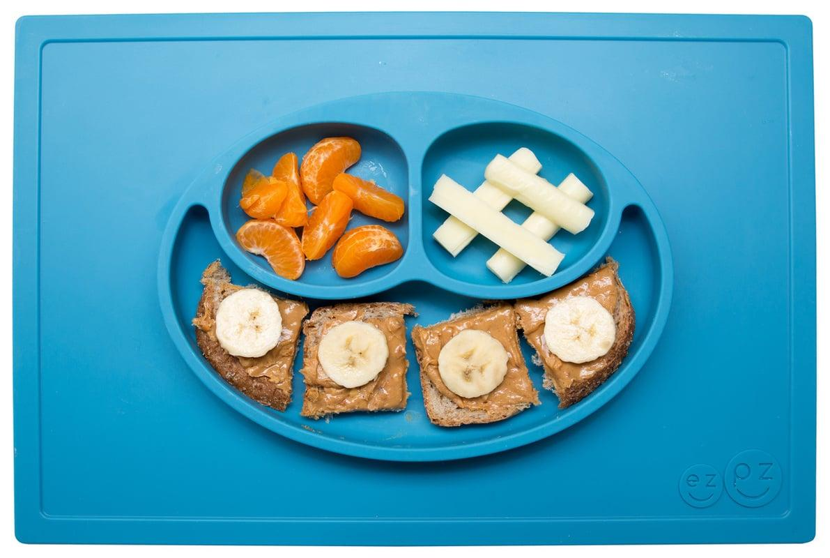 """<p>The genius folks at EZPZ were well-aware of 2-year-olds' predilection for playing with their food when they created <a href=""""https://www.popsugar.com/buy/Happy-Mat-480691?p_name=the%20Happy%20Mat&retailer=amazon.com&pid=480691&price=25&evar1=moms%3Aus&evar9=25058694&evar98=https%3A%2F%2Fwww.popsugar.com%2Fphoto-gallery%2F25058694%2Fimage%2F25571780%2FEZPZ-Happy-Mat&list1=baby%20showers%2Cbaby%20shower%20gifts%2Ckid%20shopping%2Cbaby%20shopping&prop13=api&pdata=1"""" rel=""""nofollow"""" data-shoppable-link=""""1"""" target=""""_blank"""" class=""""ga-track"""" data-ga-category=""""Related"""" data-ga-label=""""http://www.amazon.com/ezpz-Mini-Mat-One-piece-silicone/dp/B01C95ZCNI/"""" data-ga-action=""""In-Line Links"""">the Happy Mat</a> ($25), an all-in-one placemat and sectional plate that captures everything. Another clever bonus? It suctions directly to the table, making it nearly impossible for tiny hands to tip over. The food-grade silicone mat is built to last - it's bendable and flexible, and the vibrant color doesn't fade or deteriorate - and can be tossed right in the dishwasher. If you have more than one mouth to feed, simply fill each mat with fruit and veggies and stack them on top of each other to carry to the table. Easy-peasy, indeed. </p> <p>- <em>Kate Schweitzer, senior editor</em></p>"""
