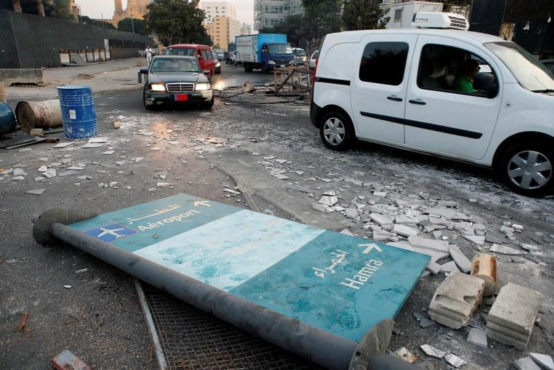 Cars drive past debris at a site of protest that happened yesterday over deteriorating economic situation