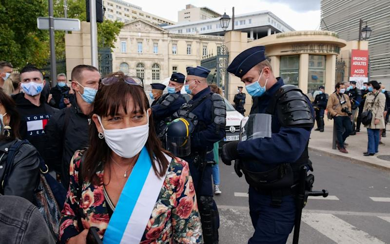 Demonstrators protest in front of La Timone hospital after French authorities announced that they order cafes and restaurants to shut down for two weeks to curb the spread of the virus - Reuters