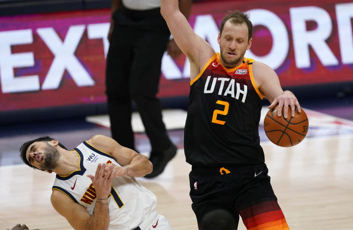 Utah Jazz forward Joe Ingles, right, drives past Denver Nuggets guard Facundo Campazzo in the first half of an NBA basketball game Sunday, Jan. 31, 2021, in Denver. (AP Photo/David Zalubowski)
