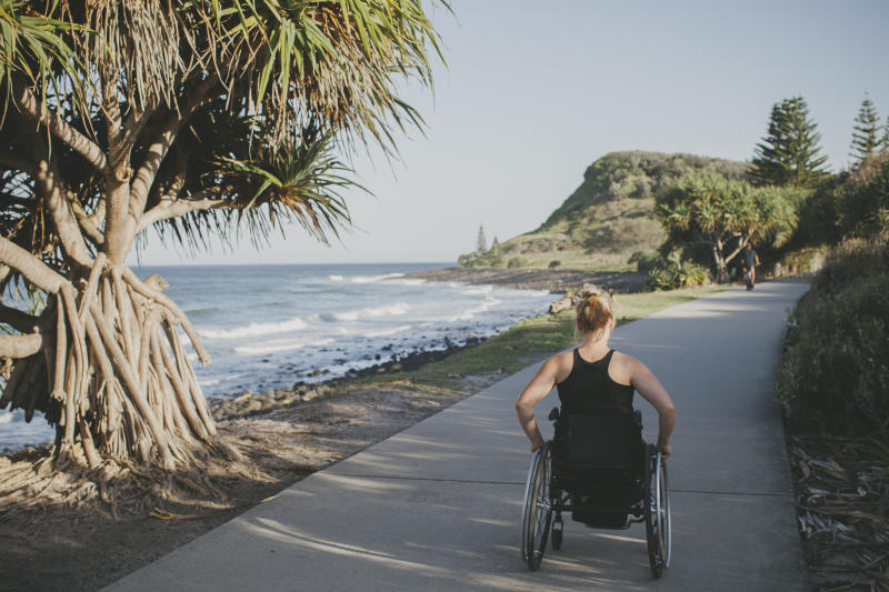 Pictured is a paraplegic woman travelling in her wheelchair beside the ocean.
