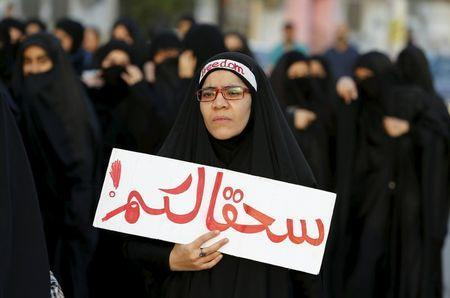 """A protester holds a banner saying """"to hell with you"""" as she takes part in a protest against the execution of Saudi Shi'ite cleric Nimr al-Nimr by Saudi authorities, in the village of Sanabis, west of Manama, Bahrain January 2, 2016. REUTERS/Hamad I Mohammed"""