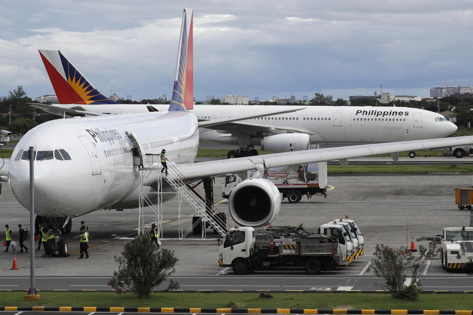 FILE PHOTO: A woman exits a Philippine Airline plane at the airport in Manila, Philippines on Tuesday, Oct. 6, 2020. Philippine Airlines has called on its employees to apply for voluntary separation from the flag carrier in the first stage of a retrenchment plan it says may affect up to 35% of its 7,000 strong work force largely due to the coronavirus pandemic. (AP Photo/Aaron Favila)