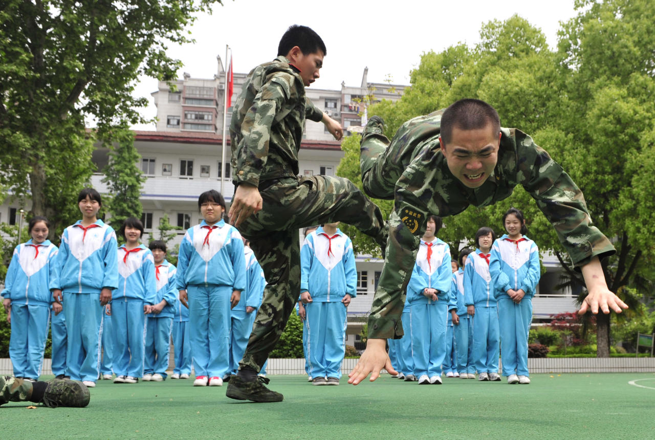 Paramilitary policemen demonstrate self-defence skills to students at a school in Nanjing, Jiangsu province May 6, 2010. China's police forces nationwide were ordered to step up security of kindergartens and schools after a spate of violent attacks against school children last week, Xinhua News Agency reported.  REUTERS/Stringer (CHINA - Tags: MILITARY EDUCATION IMAGES OF THE DAY) CHINA OUT. NO COMMERCIAL OR EDITORIAL SALES IN CHINA