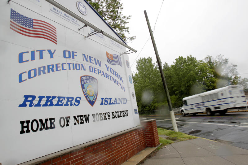 FILE- In this May 17, 2011 file photo, a New York City Department of Corrections bus passes the sign at the entrance to the Rikers Island correction facility in New York. The department of correction runs three separate bus services, one for Rikers staff who park at a central parking lot, one for visitors to the island and a third to usher inmates to and from courthouses throughout the five boroughs. (AP Photo/Seth Wenig, File)