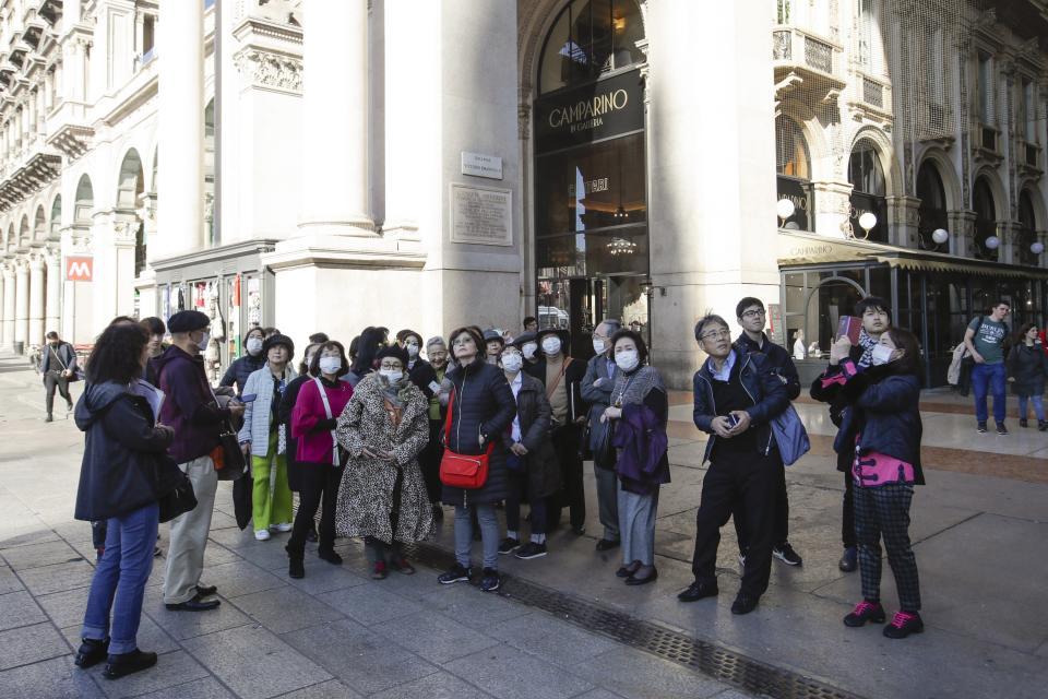 Tourists, some of them wearing sanitary masks, stand next to the Vittorio Emanuele Gallery in downtown Milan, Italy, Monday, Feb. 24, 2020. Italy has been scrambling to check the spread of Europe's first major outbreak of the new viral disease amid rapidly rising numbers of infections and a third death, calling off the popular Venice Carnival, scrapping major league soccer matches in the stricken area and shuttering theaters, including Milan's legendary La Scala. (AP Photo/Luca Bruno)