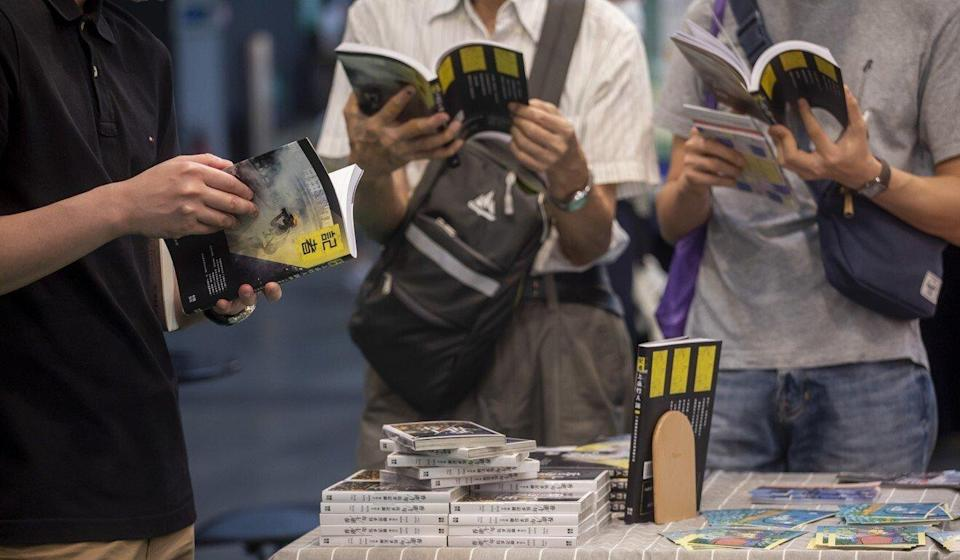 Visitors at the Hong Kong Book Fair read copies of a book documenting the experiences of journalists covering the 2019 protests. Photo: Bloomberg