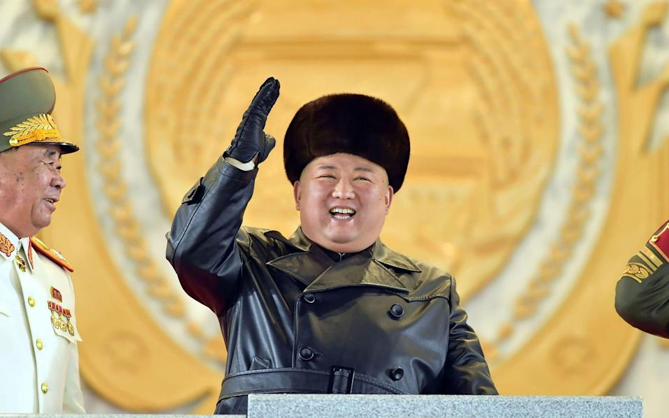 Kim Jong-un looked joyful as he presided over a parade of new weapons - AFP