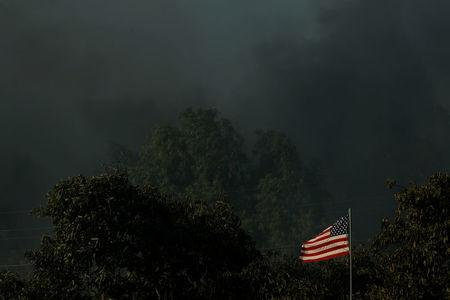 A home burns to the ground as its U.S. flag blows in the wind while the Lilac Fire burns through Bonsall, California, U.S., December 7, 2017.      REUTERS/Mike Blake