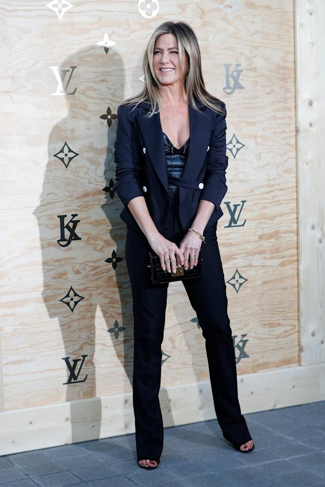 <p>Aniston, who attended the event with her husband Justin Theroux, chose a tailored suit with a hint of a leather bustier underneath in her favorite color. <i>(Photo: Reuters)</i> </p>