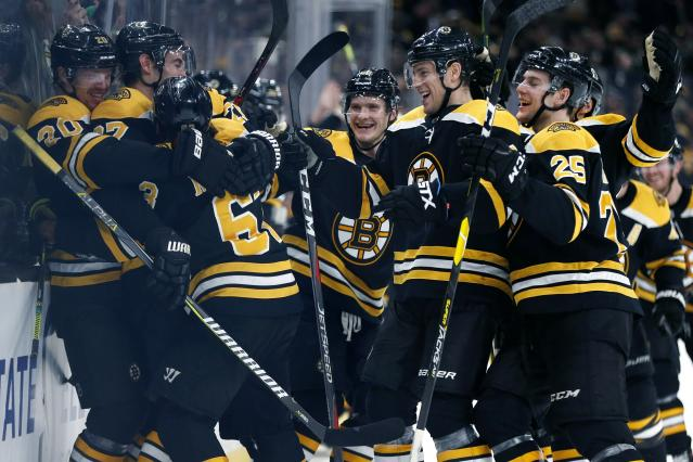 Boston Bruins celebrate after a goal by Brad Marchand (63) during overtime in an NHL hockey game against the Columbus Blue Jackets in Boston, Saturday, March 16, 2019. (AP Photo/Michael Dwyer)