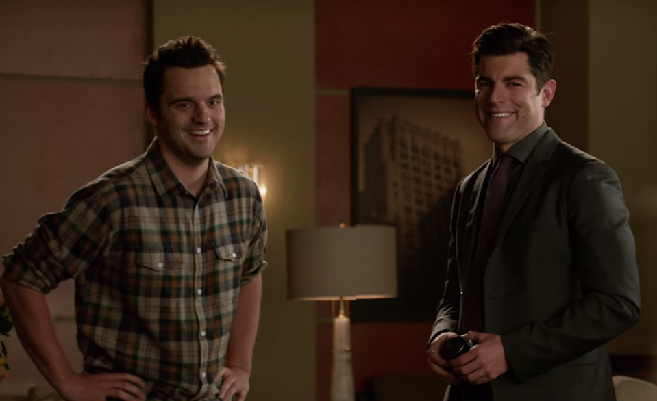 Nick Miller, smiling with hands on hips, wears a brown, red, and green checkered flannel shirt while Schmidt wears a dark-gray suit