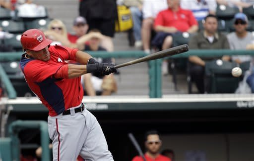 Washington Nationals' Ian Desmond hits an RBI-single driving in Bryce Harper during the first inning of an exhibition spring training baseball game against the Atlanta Braves Tuesday, Feb. 26, 2013, in Kissimmee, Fla. (AP Photo/David J. Phillip)