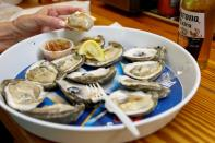 A customer at Lynn's Quality Oysters in Eastpoint, Florida, U.S., eats raw oysters from Texas at the restaurant