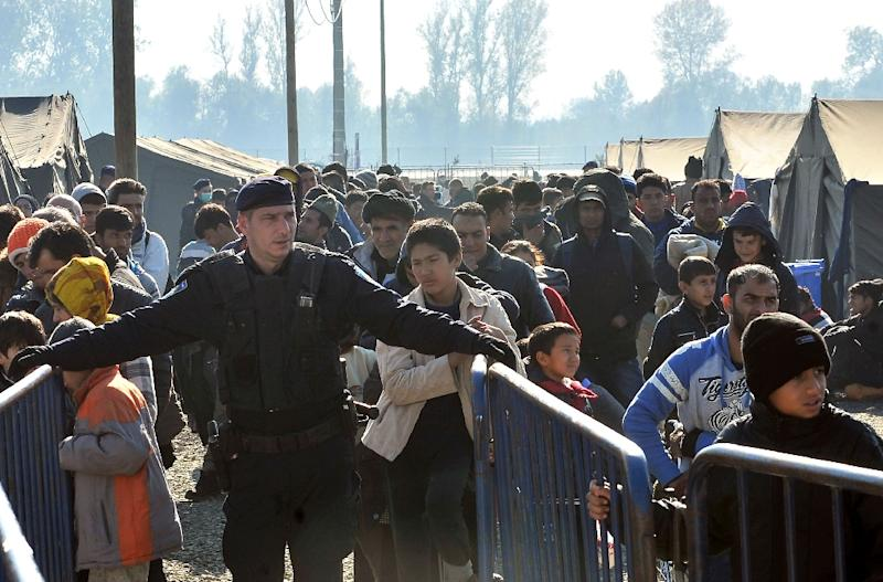 A Croatian policeman stands guard as migrants and refugees queue to enter a transit camp in Slavonski Brod on November 4, 2015 (AFP Photo/Elvis Barukcic)