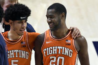 Illinois guards Andre Curbelo (5) and Da'Monte Williams (20) celebrate the team's win over Iowa in an NCAA college basketball game Friday, Jan. 29, 2021, in Champaign, Ill. (AP Photo/Holly Hart)