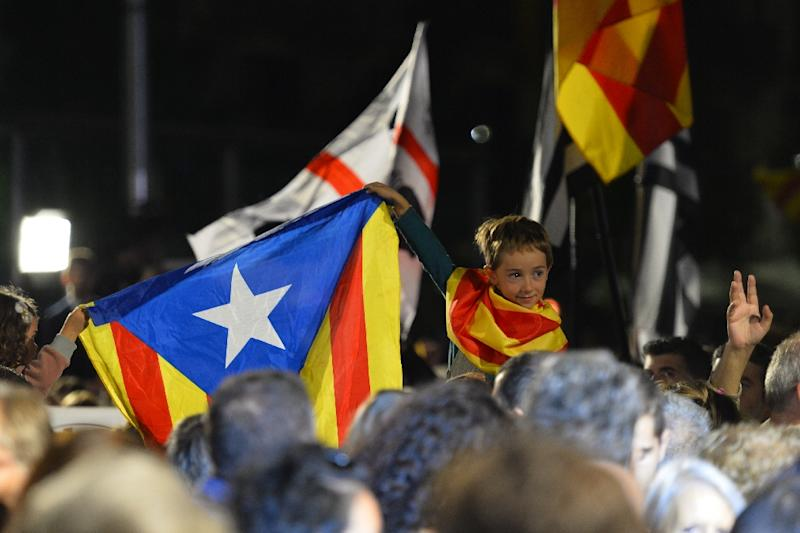 """A child holds up the """"Estelada"""" (pro independence Catalan flag) during a gathering following the close of polls for the regional elections, in central Barcelona on September 27, 2015, in Spain (AFP Photo/Gerard Julien)"""