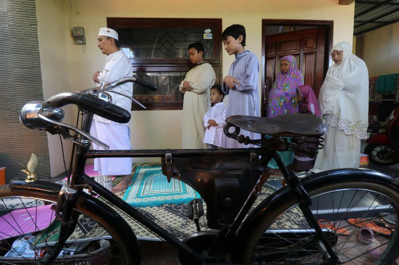 Indonesian Muslims take part in prayers during Eid al-Fitr, the Muslim festival marking the end the holy fasting month of Ramadan, at a their home amid the spread of coronavirus disease (COVID-19)