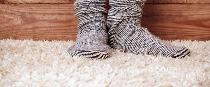 Legs of a woman in gray socks on the carpet on the wooden background. Vintage toning