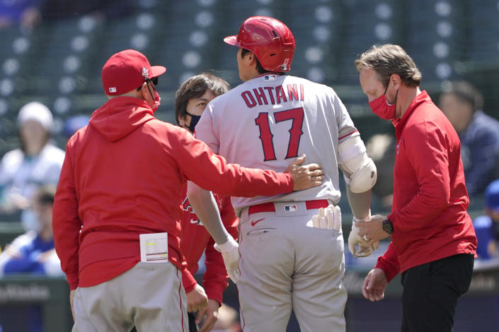 Los Angeles Angels Shohei Ohtani (17), talks with a trainer, right, and manager Joe Maddon, left, after he was hit by a pitch during the first inning of a baseball game against the Seattle Mariners, Sunday, May 2, 2021, in Seattle. Ohtani stayed in the game. (AP Photo/Ted S. Warren)