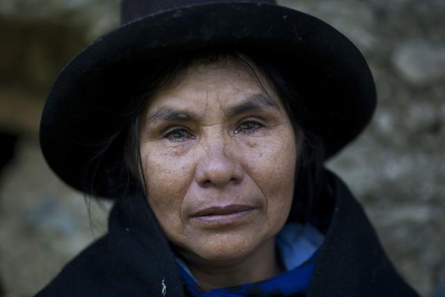 <p>Eudicia Urbano, 70, standing in front of her former home, near the spot where her husband Marcial Escalante died, weeps as she retells how he was tortured and killed by Shining Path rebels, in Chaca, Peru on June 16, 2013. (Photo: Rodrigo Abd/AP) </p>