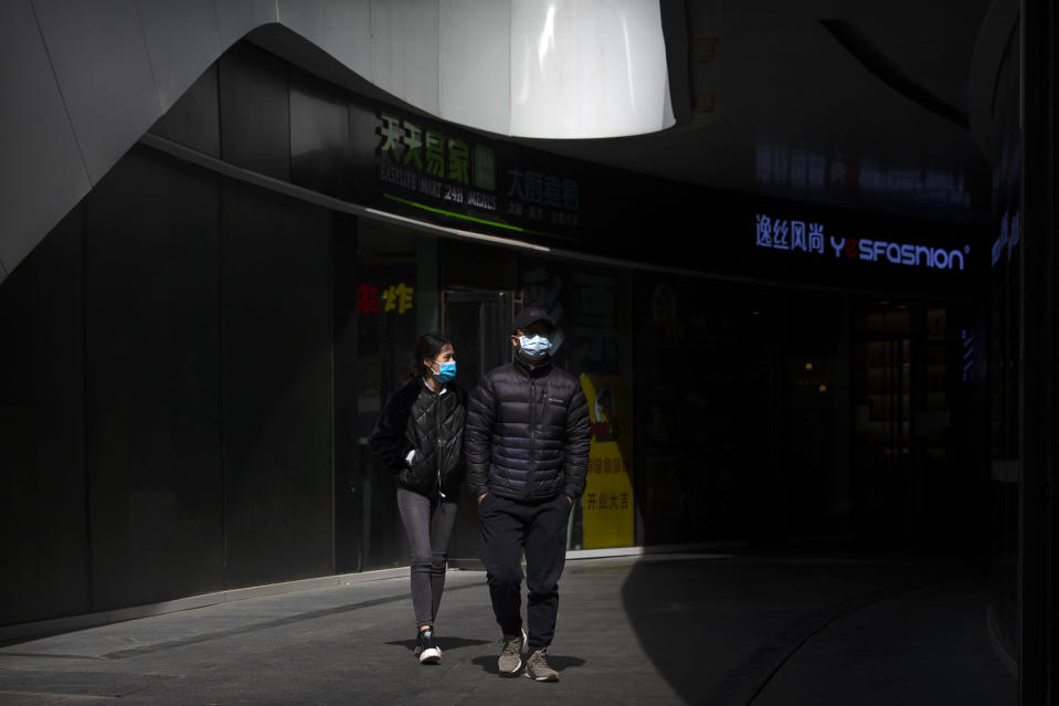 People wear face masks as they walk through an office complex in Beijing, Friday, March 20, 2020. Italy's deaths from the coronavirus pandemic eclipsed China's on Thursday as the scourge extended its march across the West, where the United States and other countries increasingly enlisted the military to prepare for an onslaught of patients and California's governor ordered people in the most-populous U.S. state to stay home. The virus causes only mild or moderate symptoms, such as fever and cough, for most people, but severe illness is more likely in the elderly and people with existing health problems. (AP Photo/Mark Schiefelbein)