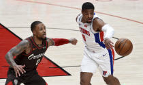 Detroit Pistons guard Dennis Smith Jr., right, pokes the ball away from Portland Trail Blazers guard Damian Lillard during the first half of an NBA basketball game in Portland, Ore., Saturday, April 10, 2021. (AP Photo/Steve Dykes)