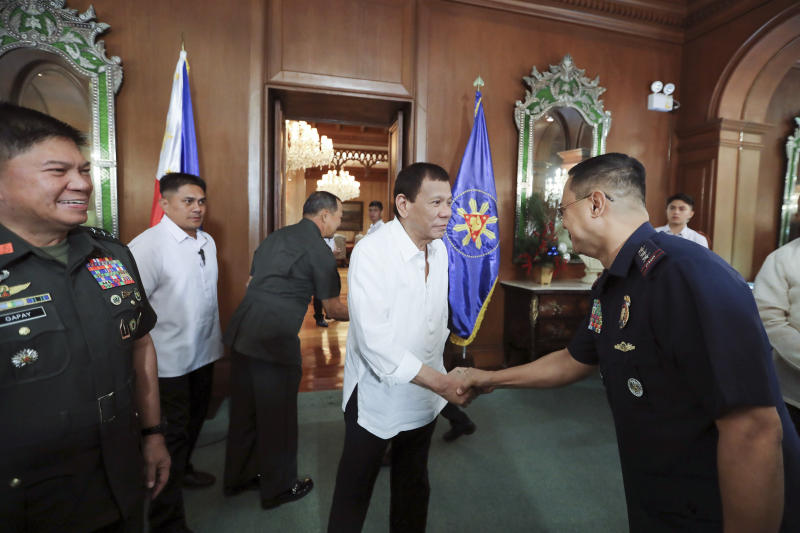 """In this Jan. 5, 2020, handout photo provided by the Malacanang Presidential Photographers Division, Philippine President Rodrigo Duterte, center, greets security officials at the Malacanang presidential palace in Manila, Philippines. Duterte has ordered the military to prepare to deploy its aircraft and ships """"at any moment's notice"""" to evacuate thousands of Filipino workers in Iraq and Iran should hostilities erupt there. (Alfred Frias/ Malacanang Presidential Photographers Division via AP)"""