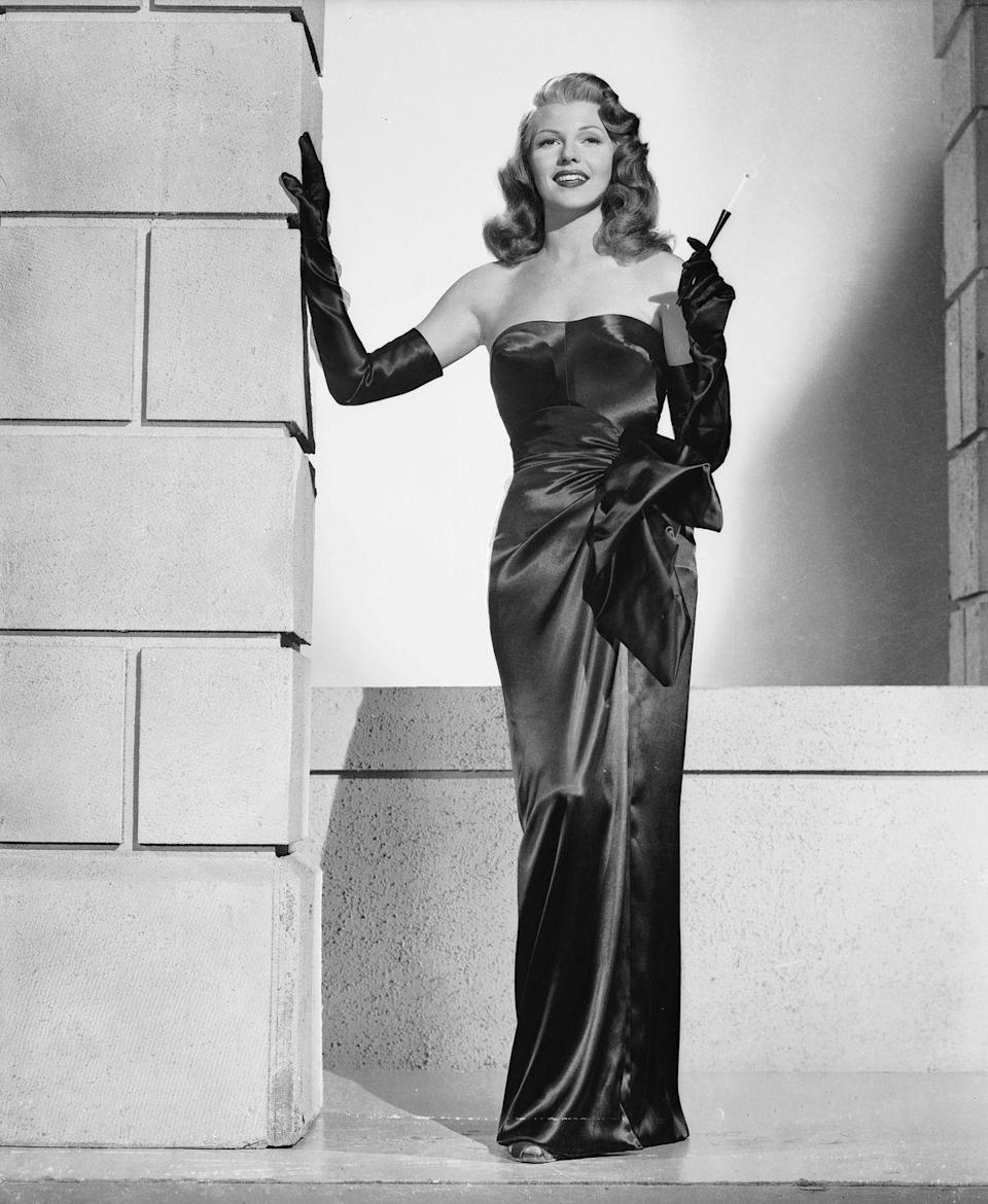 """<p>To play a 1940s pinup in <em>Gilda</em><em>,</em> Rita Hayworth wore a strapless black satin gown with matching elbow-length gloves. The film launched Hayworth into the stratosphere, although the star always <a href=""""https://www.independent.co.uk/arts-entertainment/films/features/rita-hayworth-100th-birthday-hollywood-star-gilda-actress-dancer-orson-welles-fred-astaire-a8581371.html"""" rel=""""nofollow noopener"""" target=""""_blank"""" data-ylk=""""slk:struggled with being compared"""" class=""""link rapid-noclick-resp"""">struggled with being compared</a> to her sex-symbol character. </p>"""
