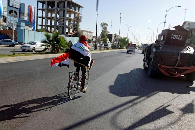 <p>A man rides a bicycle with Iraqi flag in north of Kirkuk, Iraq, Oct. 19, 2017. (Photo: Ako Rasheed/Reuters) </p>