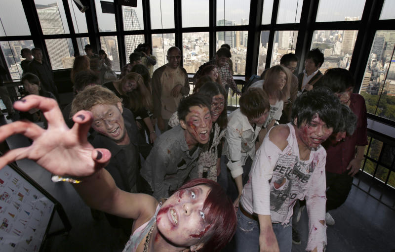 Participants wearing zombie makeups perform during a Halloween event at Tokyo Tower in Tokyo, Thursday, Oct. 31, 2013. (AP Photo/Shizuo Kambayashi)