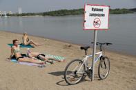 People relax on a city beach. From 12 May, the Novosibirsk authorities have extended the self-isolation regime with an easing of lockdown measures. The Russian Federal Service for Surveillance on Consumer Rights Protection and Human Wellbeing (Rospotrebnadzor) allows people to engage in sports and physical activities in pairs or alone observing social distancing. People may walk in city streets in pairs or with members of their families except for visiting public places and playgrounds. Visits to cemeteries in the Novosibirsk Region are also permitted. Kirill Kukhmar/TASS (Photo by Kirill Kukhmar\TASS via Getty Images)