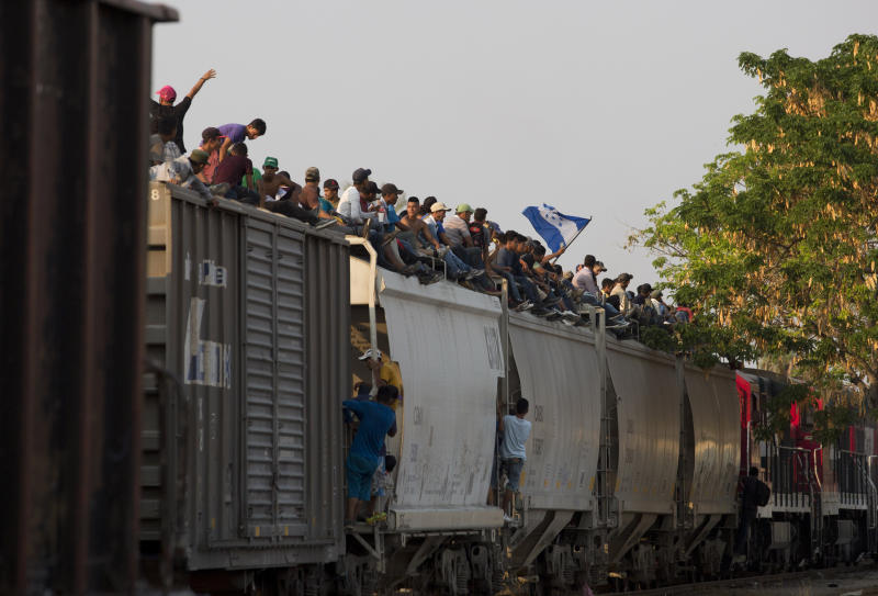 FILE - In this April 23, 2019, file photo, Central American migrants ride atop a freight train during their journey toward the U.S.-Mexico border, in Ixtepec, Oaxaca State, Mexico. Five American journalists brought a lawsuit Wednesday, Nov. 20, 2019, against the U.S. government that alleges border authorities violated their First Amendment rights by inspecting their cameras and notebooks and questioning them extensively about their coverage of last year's migrant caravan. The lawsuit seeks to test the limits of broad authority that U.S. officials have to question anyone, including journalists, who arrive by land, air or sea. (AP Photo/Moises Castillo, File)