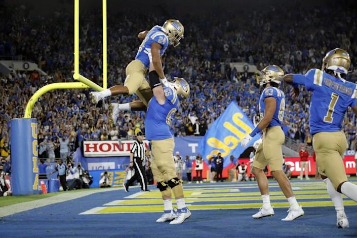 PASADENA, CA - SEPTEMBER 18, 2021: UCLA Bruins offensive lineman Paul Grattan (65) lifts up UCLA Bruins running back Zach Charbonnet (24) after Charbonnet scored in the first half against Fresno State at the Rose Bowl on September 18, 2021 in Pasadena, California.(Gina Ferazzi / Los Angeles Times)