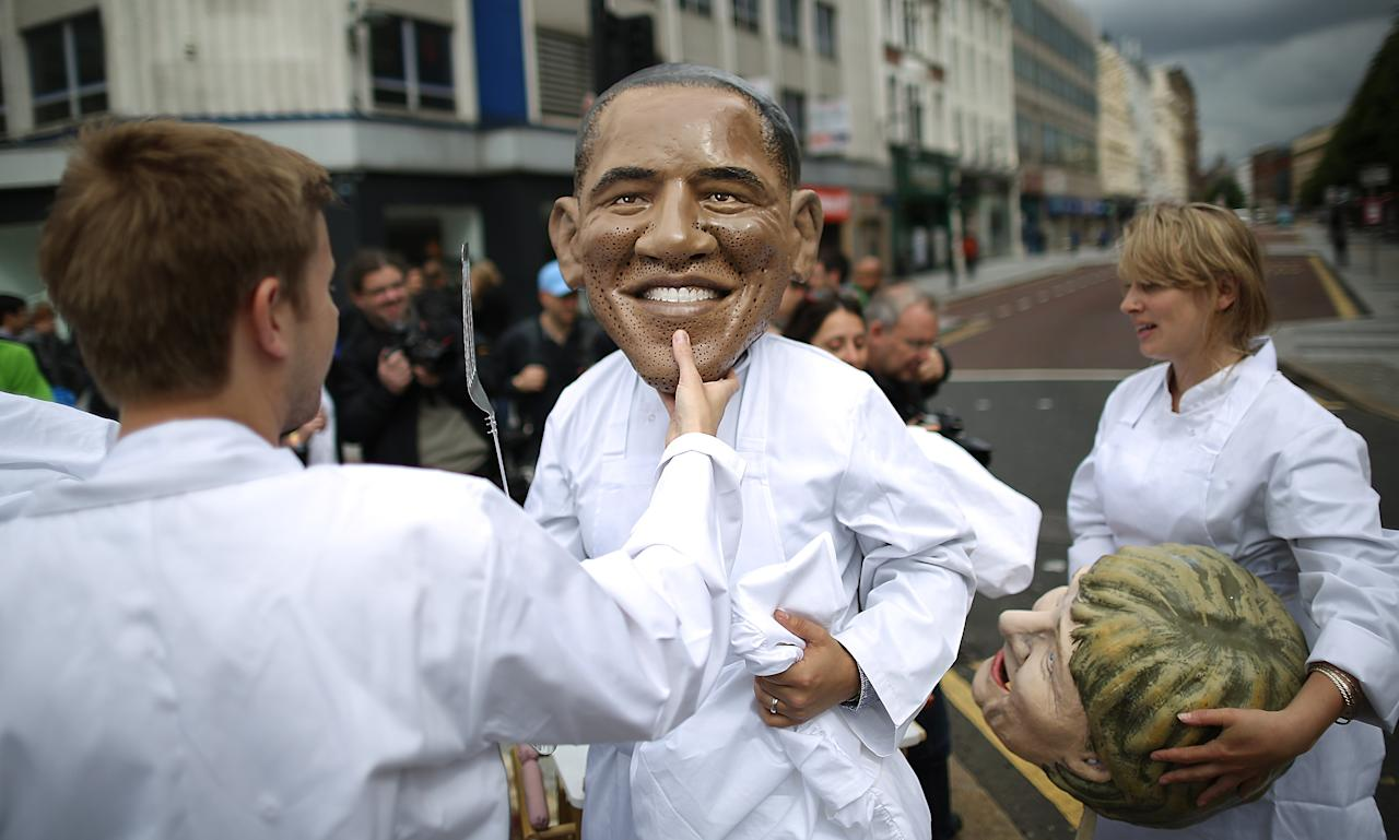 BELFAST, NORTHERN IRELAND - JUNE 16: An Oxfam worker helps another remove his mask depicting US President Barack Obama after a photocall on June 16, 2013 in Belfast, Northern Ireland. The G8 group of world leaders will meet tomorrow in Fermanagh, Northern Ireland. (Photo by Peter Macdiarmid/Getty Images)