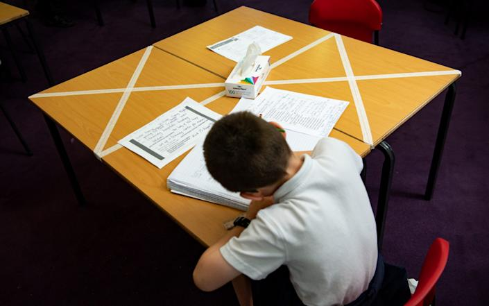 Social distancing measures are enforced as a child studies at a marked table at Kempsey Primary School in Worcester - PA
